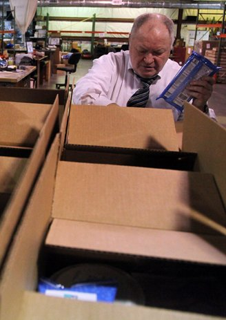 Cancer Fund of America President James Reynolds Sr., seen in 2009, examines boxes containing donated products to be distributed to cancer patients across the country.