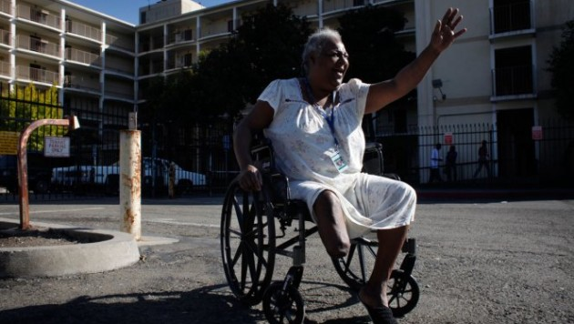 Rhonda Marshall, 58, waves to visitors outside the Hacienda public housing complex. She's been living on the high-rise's first floor for years and has watched the building deteriorate. She says she sees cracks in the walls running from the sixth floor to the ground and smells mold in the hallways and stairwells.