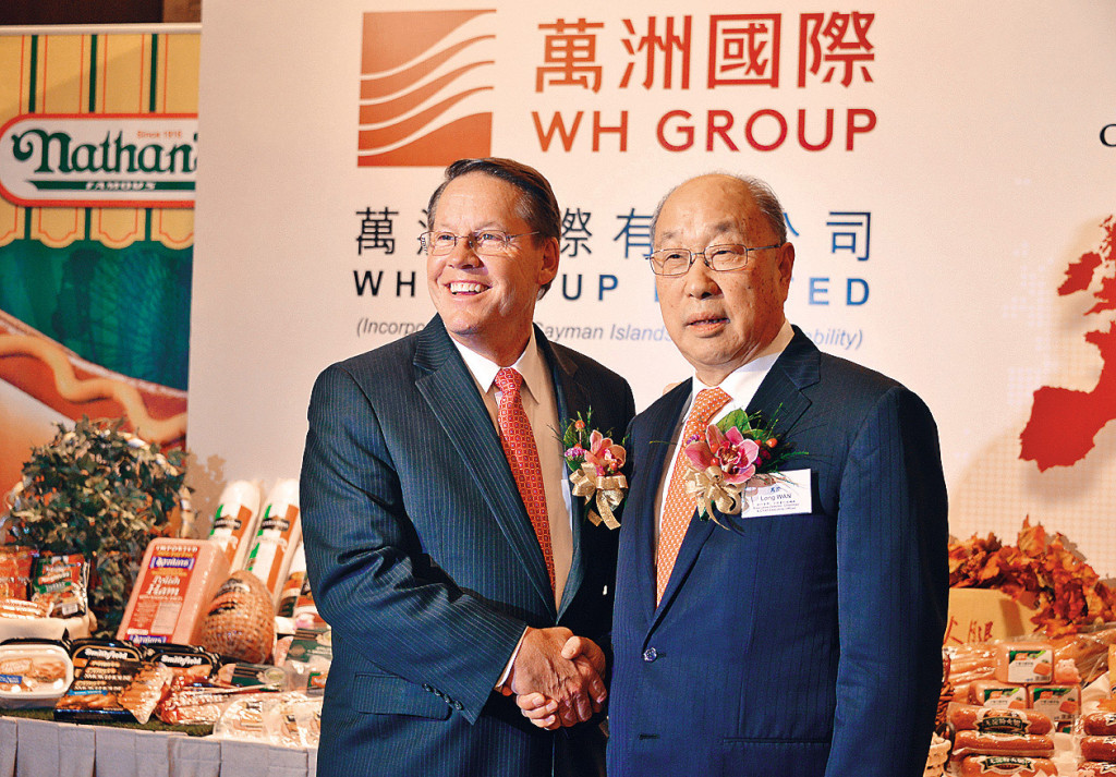 Larry Pope (left), president and CEO of Smithfield Foods, shakes hands with Wan Long, chairman and CEO of WH Group, formerly Shuanghui International, at a press conference in Hong Kong last year.