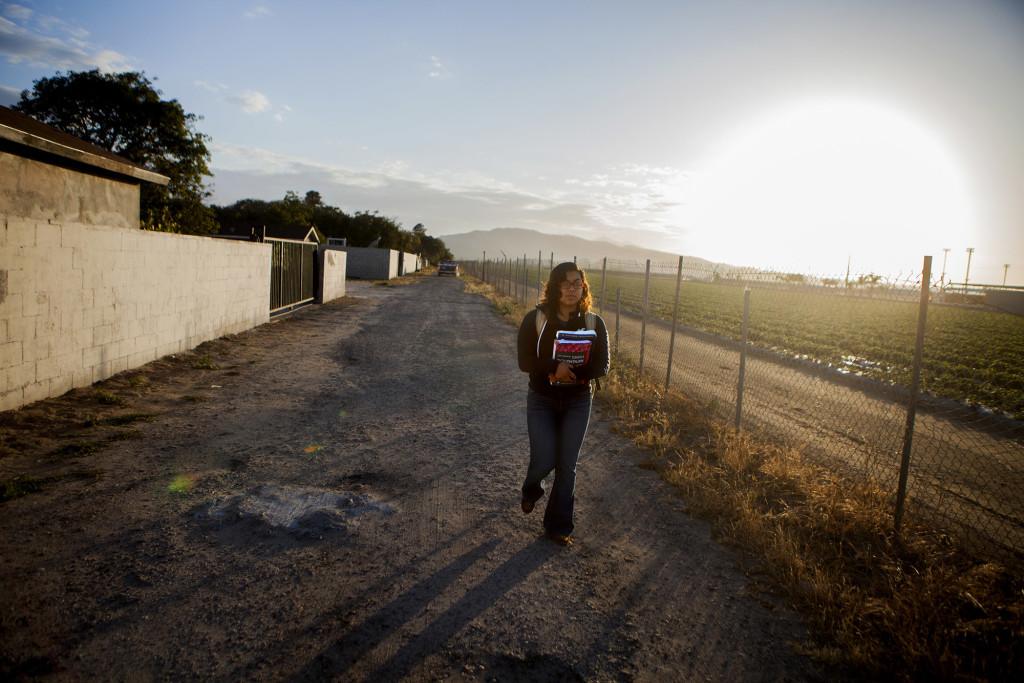 Valeria García camina junto a campos de fresas rumbo a la Escuela Secundaria Río Mesa en Oxnard, California.