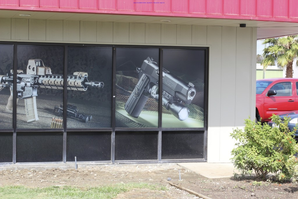 The Tracy Rifle and Pistol gun shop in Tracy, Calif., displays images of an AR-15 rifle and a .45-caliber pistol equipped with a flashlight.