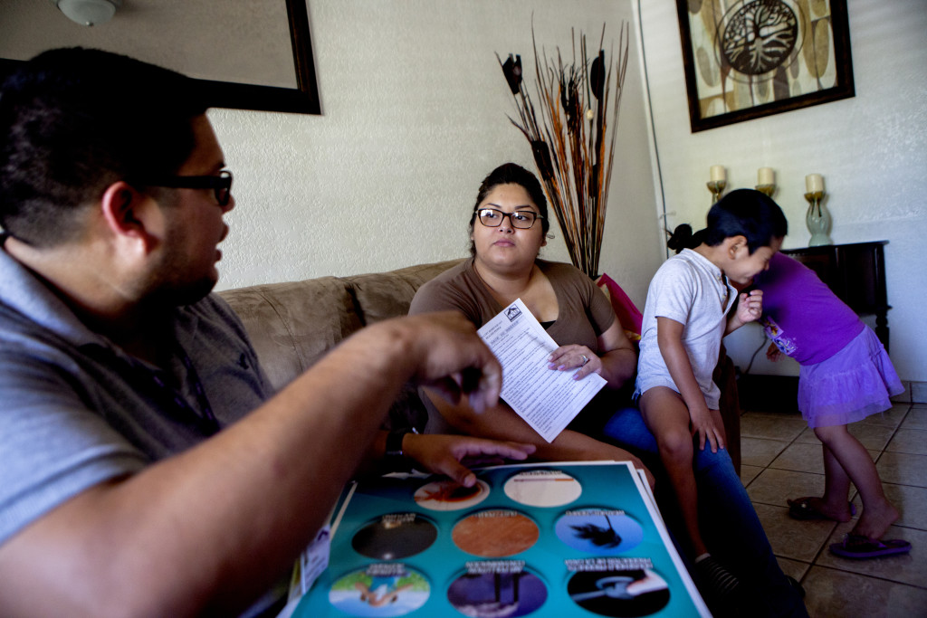 Health worker Manuel Farias (left) conducts a home visit in El Centro, Calif., with Arlene Gonzalez, whose son Franco Romero, seen here sneezing from allergies, has asthma.
