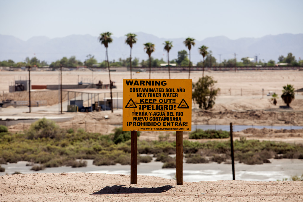 A sign warns visitors away from the polluted New River, which flows north from Mexicali, Mexico, through Calexico, Calif.