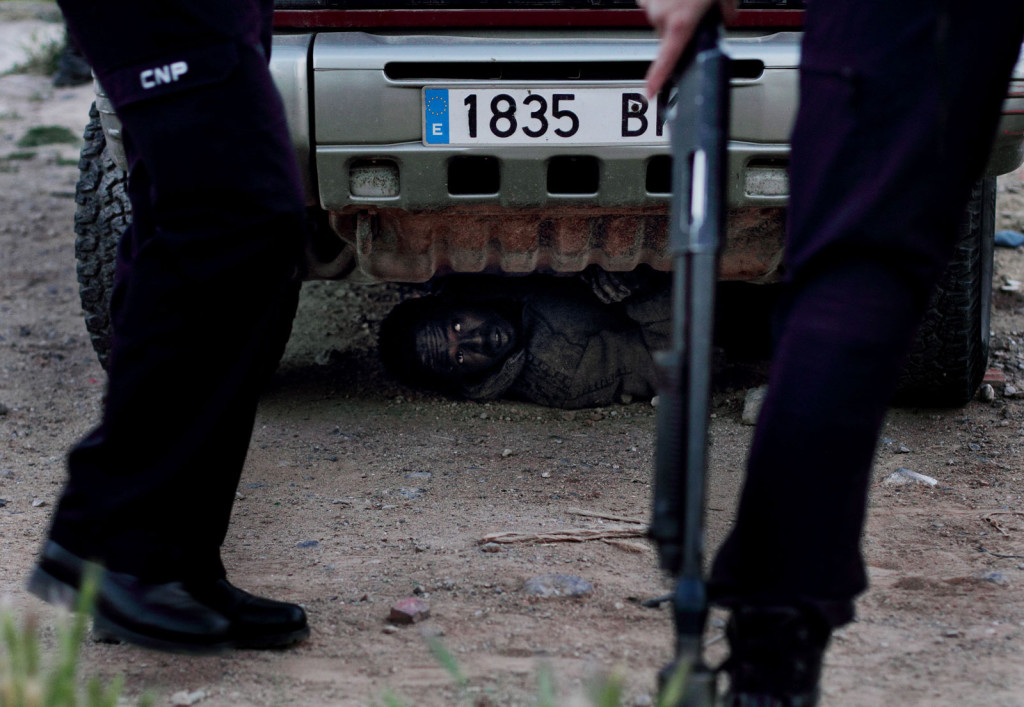 "Attempting to avoid deportation, a migrant hides from Spanish police under a car. The drive to escape detection grows from common border knowledge: Those caught often face ""express deportation"" by Spanish authorities who maintain they were stopped at the border and so never truly reached Spain."