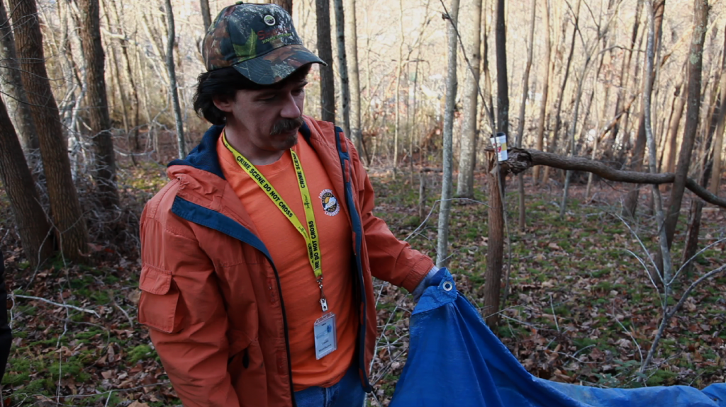 Todd Matthews, spokesman and director of case management for the National Missing and Unidentified Persons System, holds a tarp to gather dirt from a grave at an exhumation last November in Harlan, Ky.