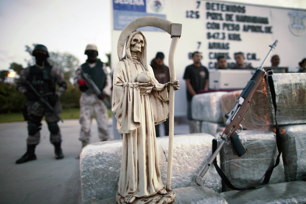 A statue of the goddess Santa Muerte sits with packages of marijuana and a gun after a drug bust in Tijuana, Mexico, in 2010. Some law enforcement agencies believe that the Mexican folk religion is linked to violent crime.