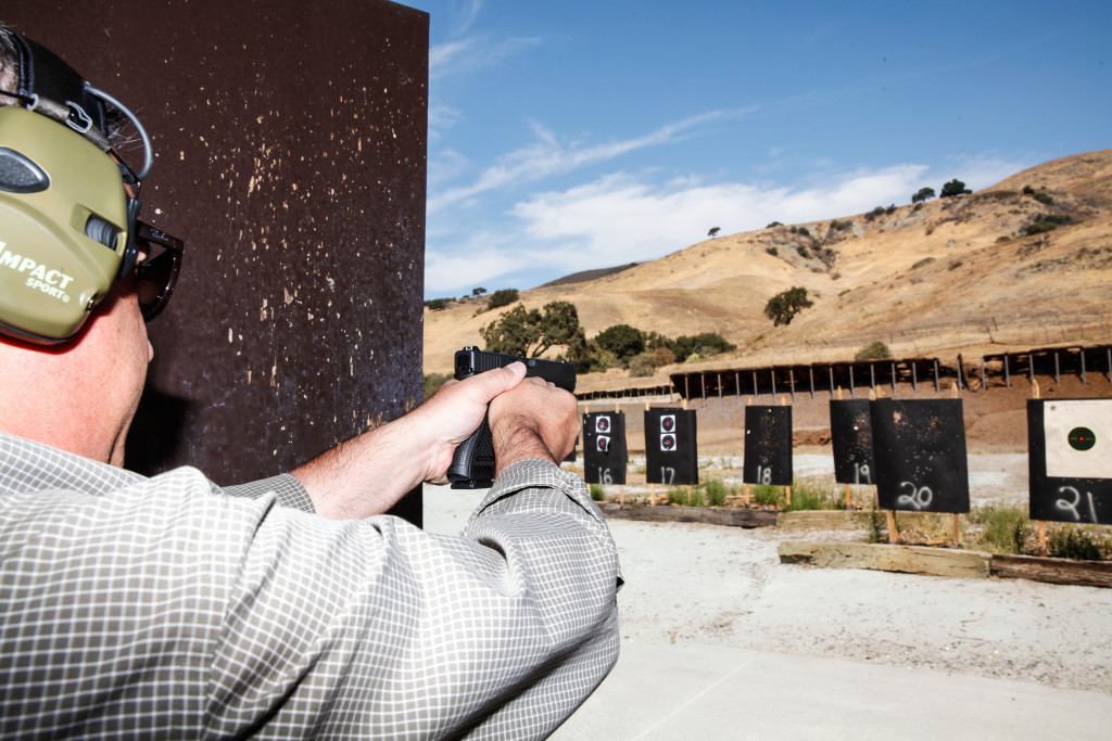 Jim Schaff, Yardarm's vice president of marketing, demonstrates a Glock .22-caliber pistol equipped with the sensor at a shooting range in San Jose, Calif. The sensor records when a gun is unholstered or fired.