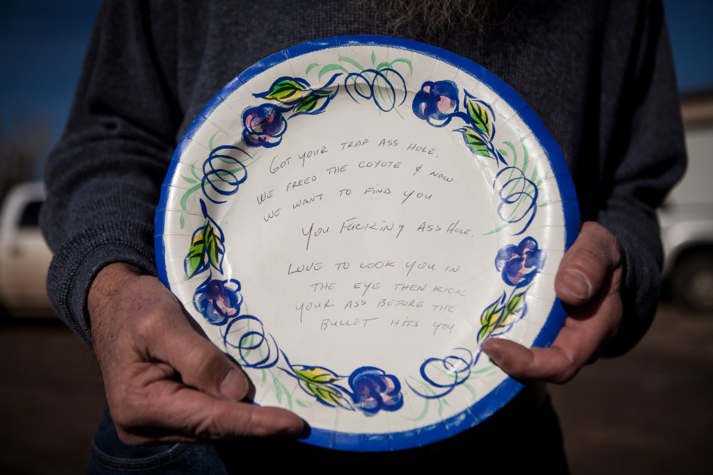 A Nevada fur trapper displays a threatening note he received on a paper plate set at one of his traps.