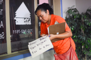 """Reynalda Cruz removes a New Jersey temp agency window sign that reads, """"Trabajo Para Mujeres,"""" or """"Work for Women."""" Cruz was a temp worker for many years before joining New Labor, a workers advocacy group."""