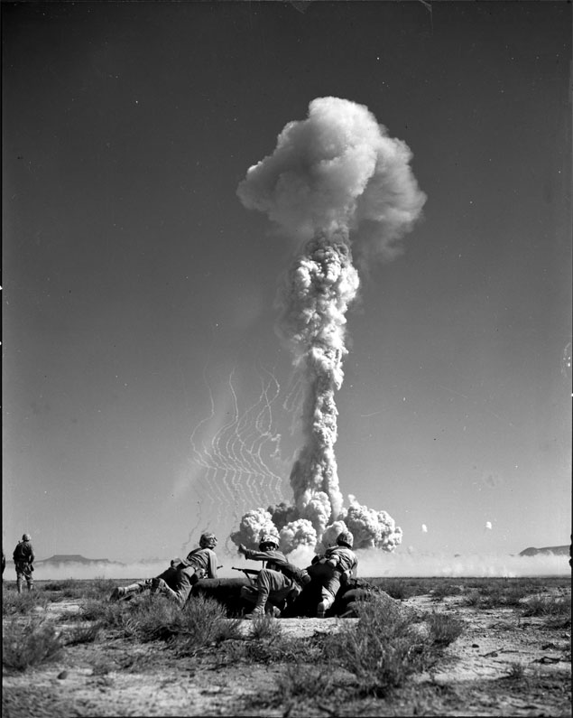 "Marines prepare to charge an ""objective"" seconds after an atomic explosion at the Atomic Proving Grounds, Yucca Flat, NV. Twenty-one hundred Marines comprised the largest number of troops to participate in the tests to date."