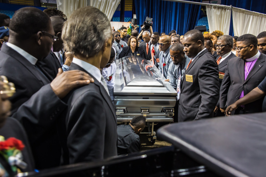 Rev. Al Sharpon next to a glass covered hearse as pallbearers load Alton Sterling's casket inside follow a public funereal attened by over 1000 people at Southern University's F.G. Clark Activity Center in Baton Rouge.
