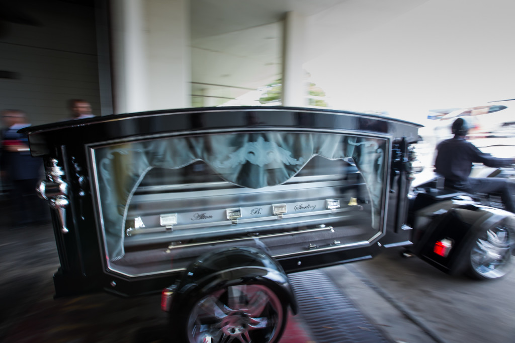 A motorcycle pulls the casket of Alton Sterling in glass covered hearse to Mount Pilgrim Benevolent Society Cemetery following his funeral in Southern University's F.G. Clark Activity Center in Baton Rouge. Over a thousand people attended the public funeral where religious leaders including Rev. Jesse Jackosn, Al Sharpton politicians, family members and friends friend's spoke.