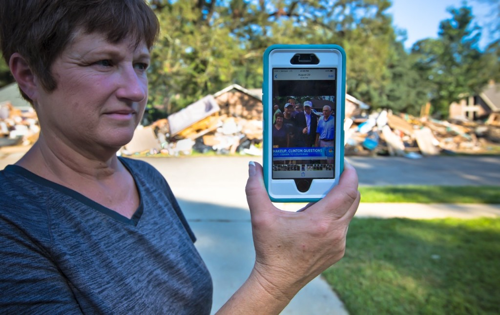 Zanie Whitehead shows a photo on Sunday of Donald Trump's Aug. 19 visit to Chaperral Drive in Denham Springs. Heaps of debris and belongings remain on the street six weeks after the flood.