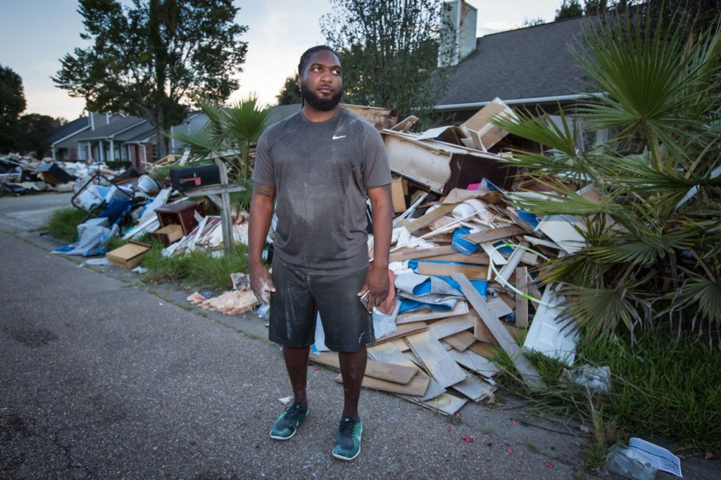 Aaron Sutton, standing outside his flooded Baton Rouge home on Sunday, compares the aftermath of the flood with Marine boot camp.