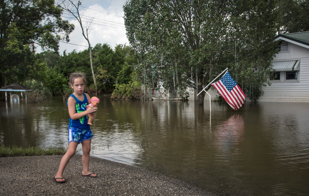 An American flag hangs above floodwater in Sorrento, Louisiana, on Aug. 20 as a girl clutches her doll.