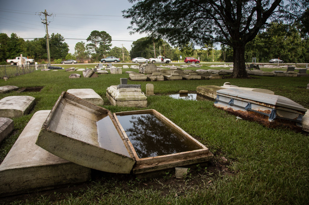 A rusted casket sits unearthed at a flooded cemetery in Zachary, Louisiana, on Aug. 20.