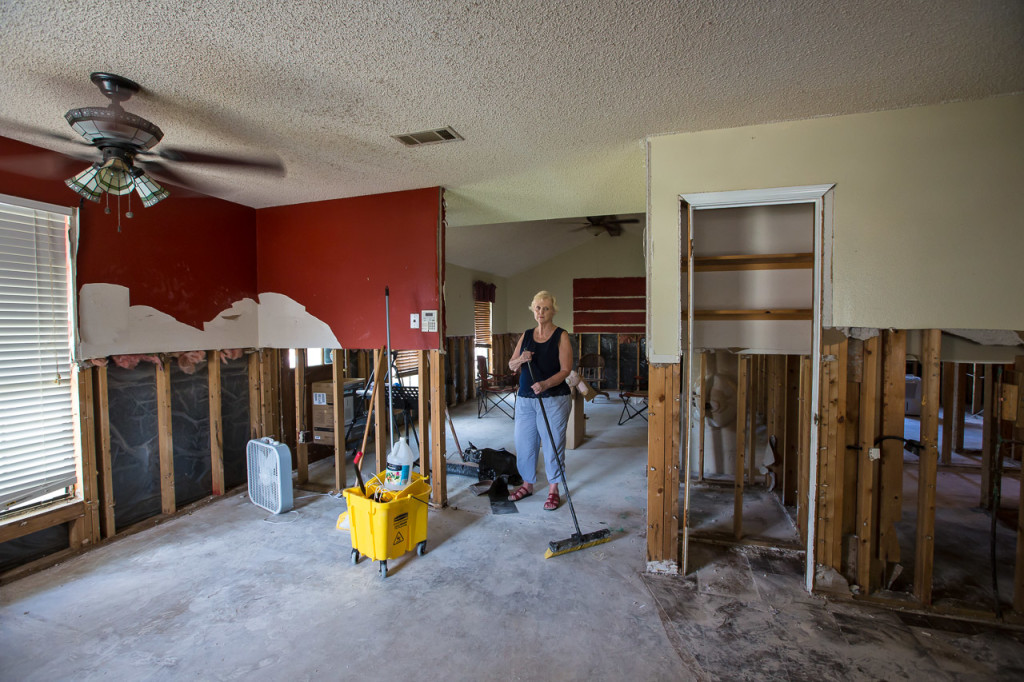 Mary Bradford, a widowed 78-year-old, cleans the gutted house she has lived in for more than 30 years about five weeks after the flood.