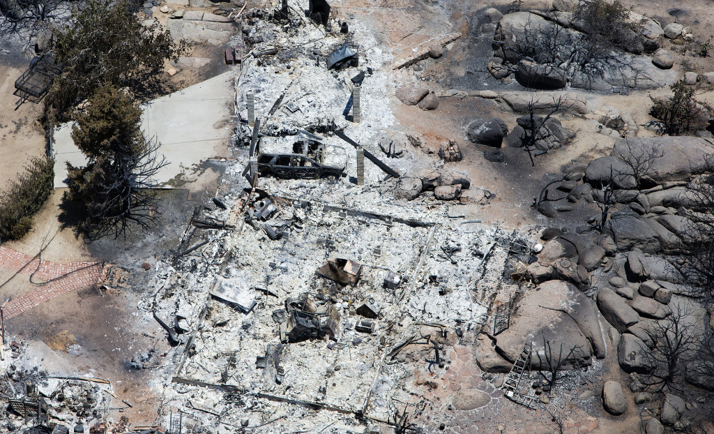 An ash-covered plot and a burned vehicle are seen from above in Yarnell, Arizona, on July 3, 2013. Nineteen Prescott firefighters died and 130 homes were destroyed in the Yarnell Hill Fire.