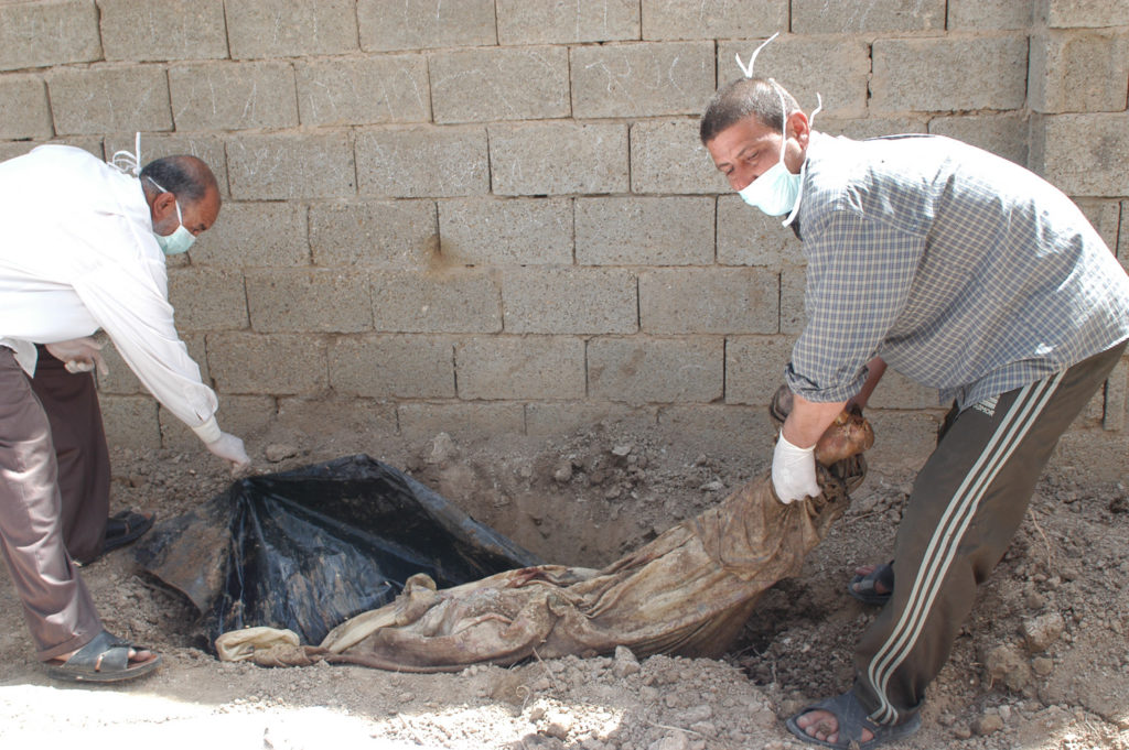 Iraqi volunteers in surgical masks pull a woman's corpse out of the front yard of a Fallujah home, where she was temporarily buried.
