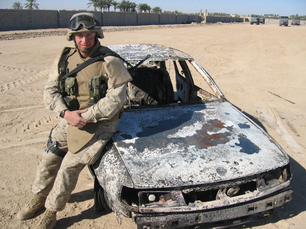 Marine Sgt. Adam Kokesh poses for a so-called trophy photo with a car that Marines shot up at a checkpoint, killing the Iraqi driver in the hail of machine-gun fire.