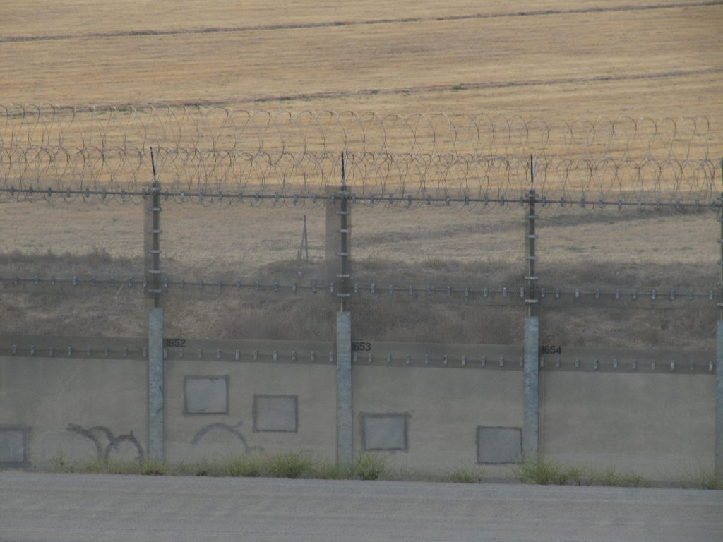 Damaged and repaired border fence, seen from the Tijuana airport.