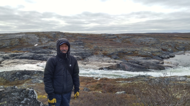Charlie Kowcharlie standing at the point where the future hydro project is planned to cross the Inukjuak River.