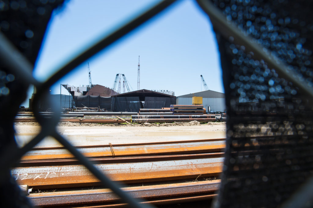 VT Halter Marine's Pascagoula, Mississippi, shipyard, seen through a hole in fencing fabric.