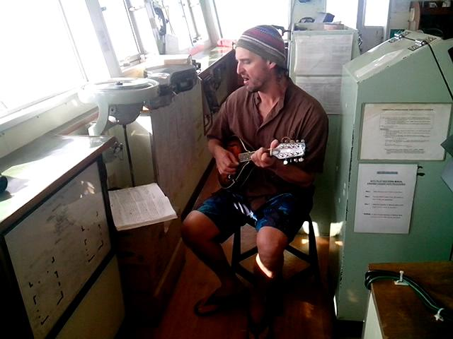 "Keith Davis plays his mandolin on the bridge of the Victoria No. 168. Davis had once written a song about observers who died at sea: ""Some say he's lost. Maybe he's been found."""