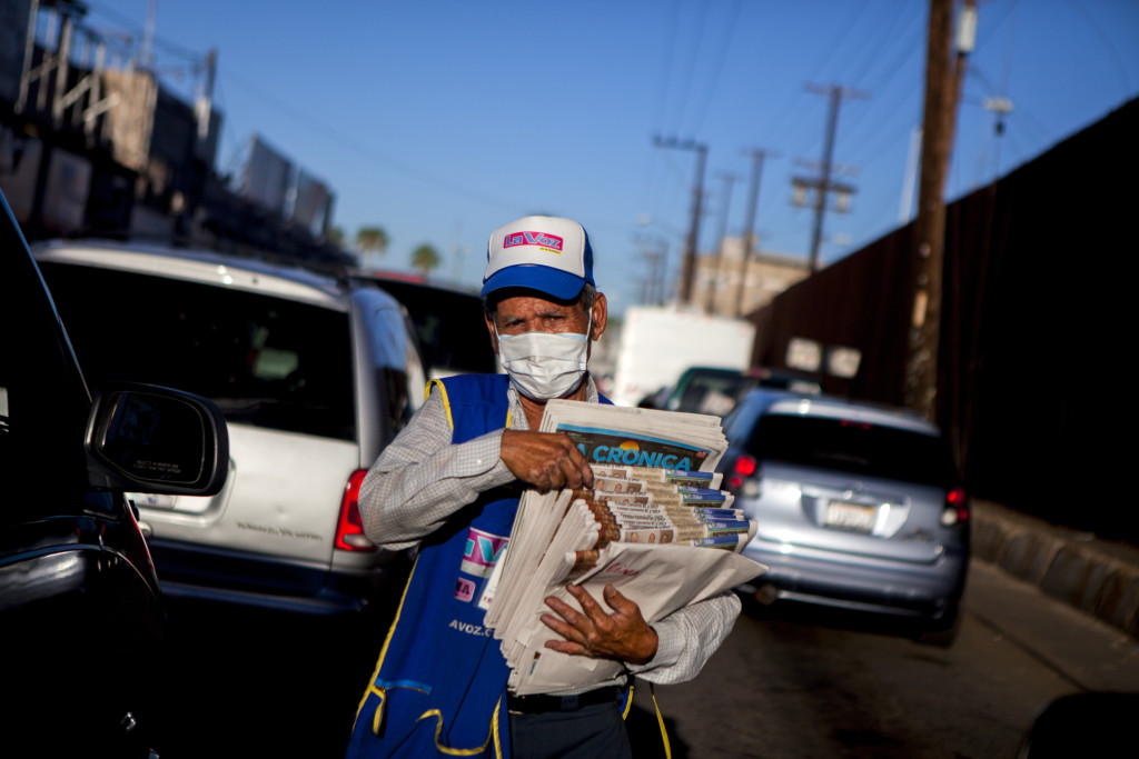 Guadalupe Catanera wears a mask to protect against car fumes as he sells newspapers to motorists waiting to cross into the United States from Mexicali, Mexico.