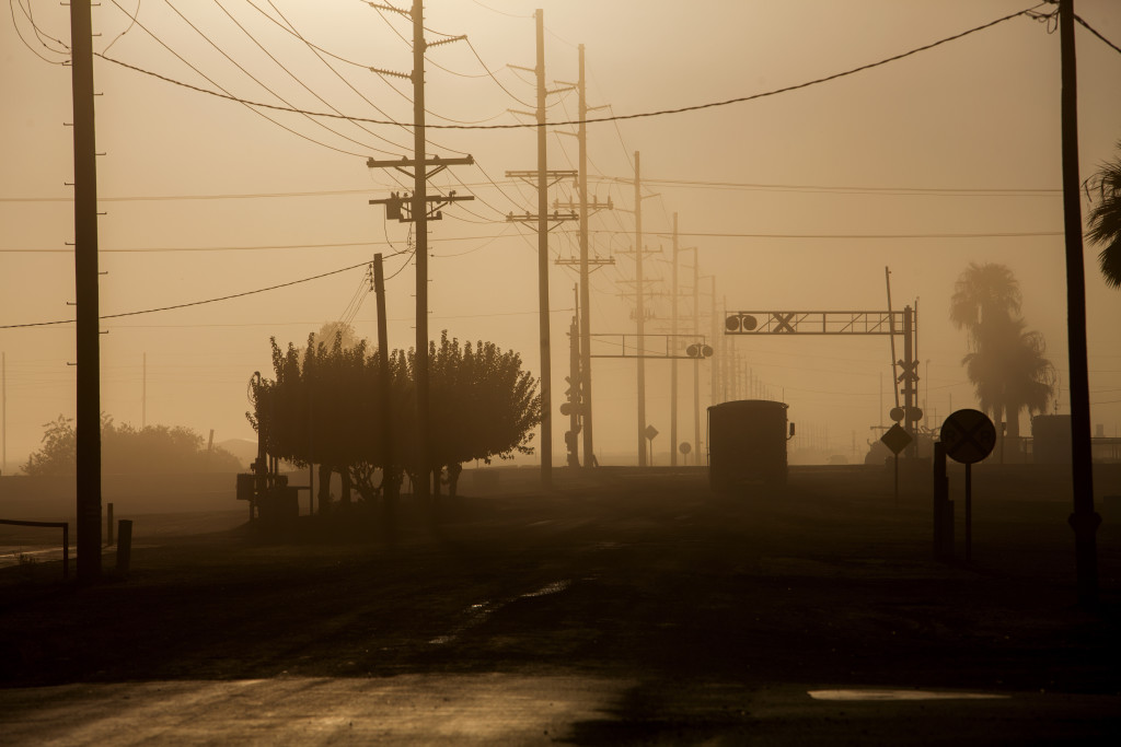 Cars drive along a dusty road in Heber, Calif. For the Imperial Valley's most vulnerable residents, the combination of poverty and poor air quality can be a potentially lethal mix.