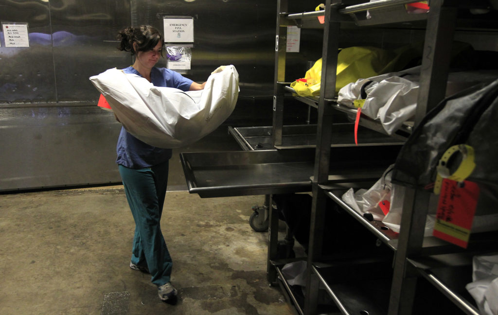 Caitlin Vogelsberg, a worker at the Pima County morgue in Arizona, carries the unidentified remains of a suspected illegal immigrant in August 2012.