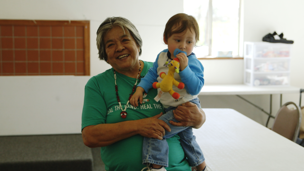 Tribal elder Priscilla Hunter beams while holding her grandson.