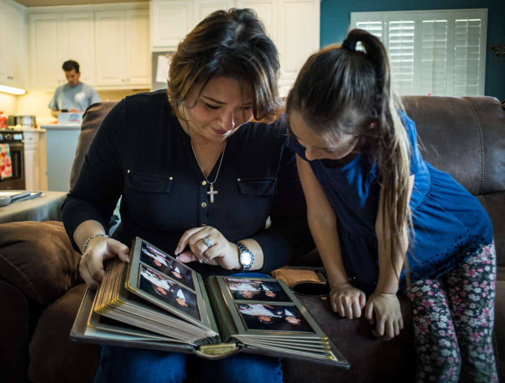 Malissa Pineda looks at a family photo album with her 7-year-old daughter, Piper Joy, who was conceived through in vitro fertilization at the Pacific Reproductive Center.