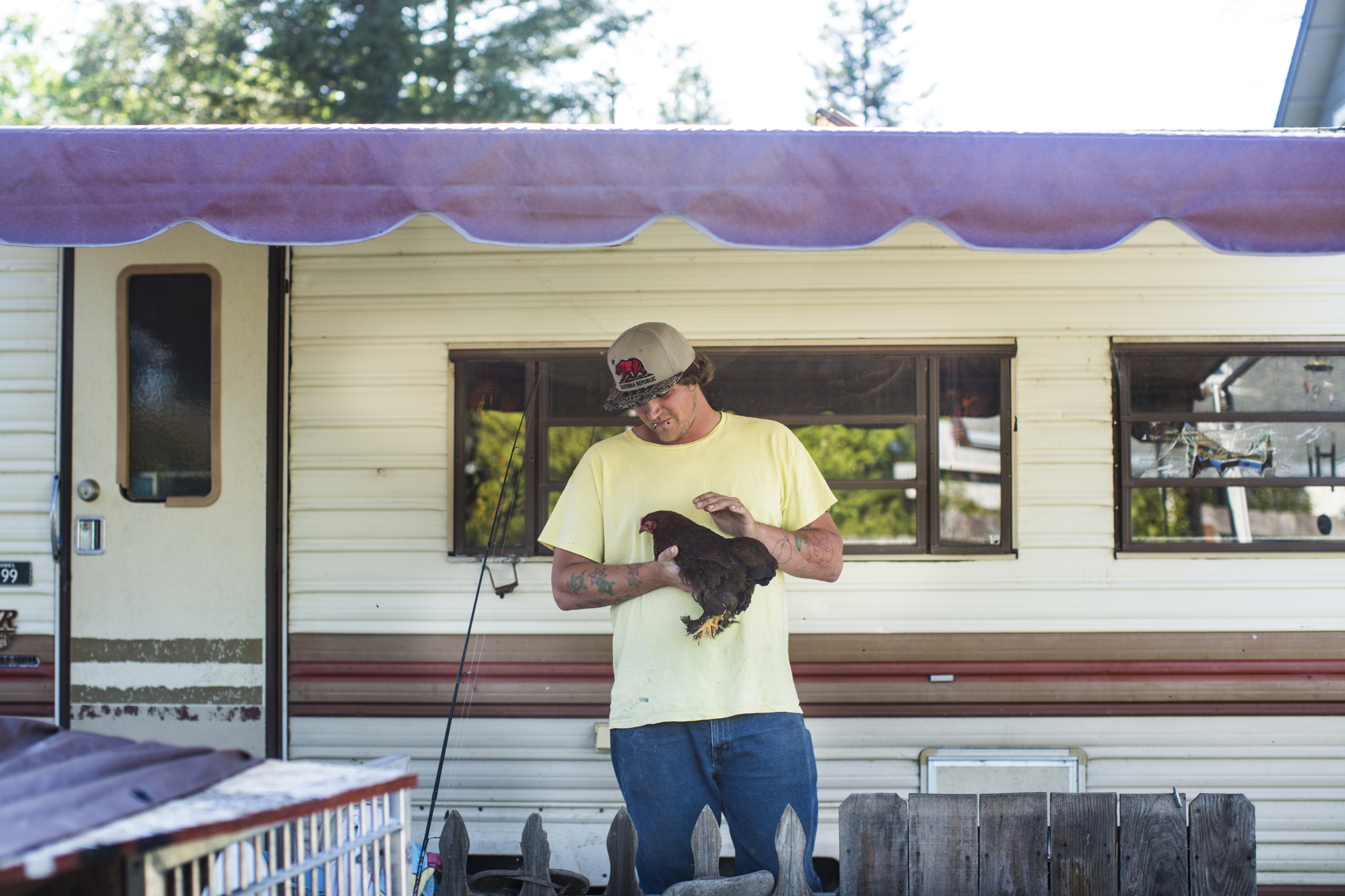 Austin Greenwood pets one of his chickens outside the trailer he is living in with his girlfriend in Windsor, Calif. Greenwood said his for-profit diversion program felt like a restaurant that prepares the same meal for everyone, no matter their needs or desires.