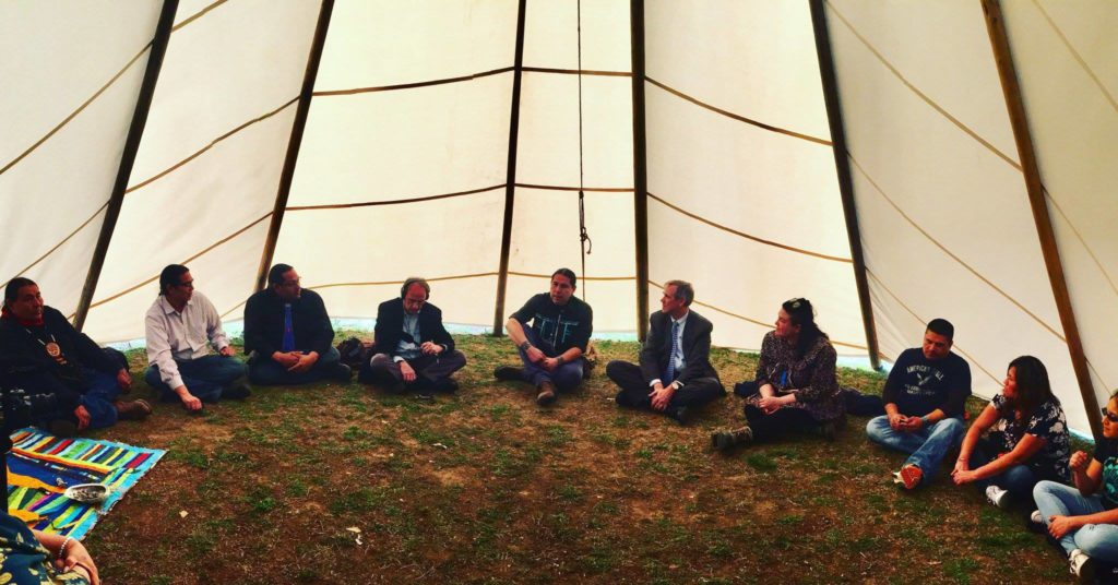 Sen. Jeff Merkley (center, in suit and tie), D-Ore., meets with tribal leaders and activists in a teepee set up on the National Mall in March to discuss their opposition to the oil industry.