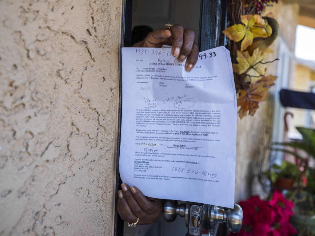 Through her front door in Los Angeles, Evelyn Knights shows a three-day eviction notice she received from Colony. Knights is on a fixed income and has needed her church's help to stay in the single-family rental home.