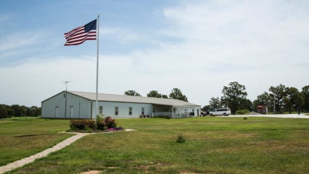 A photo of a white building with an american flag outside, against a blue sky.