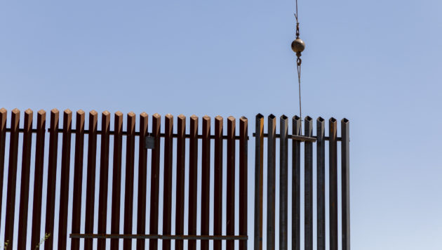 A crane lowers a section of the US/Mexico border wall into place.