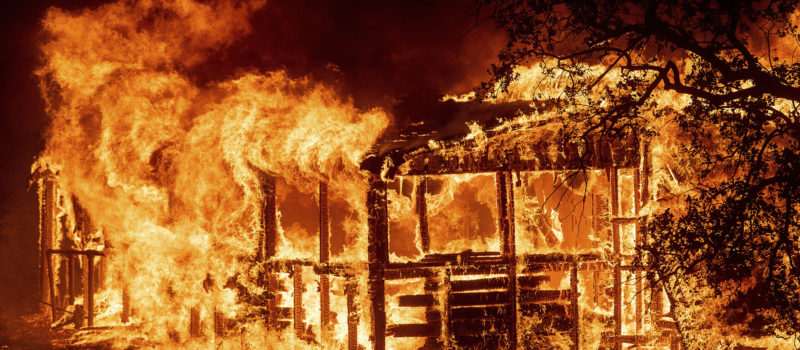 The Carr Fire burns a building along Highway 299 near Redding on Thursday.