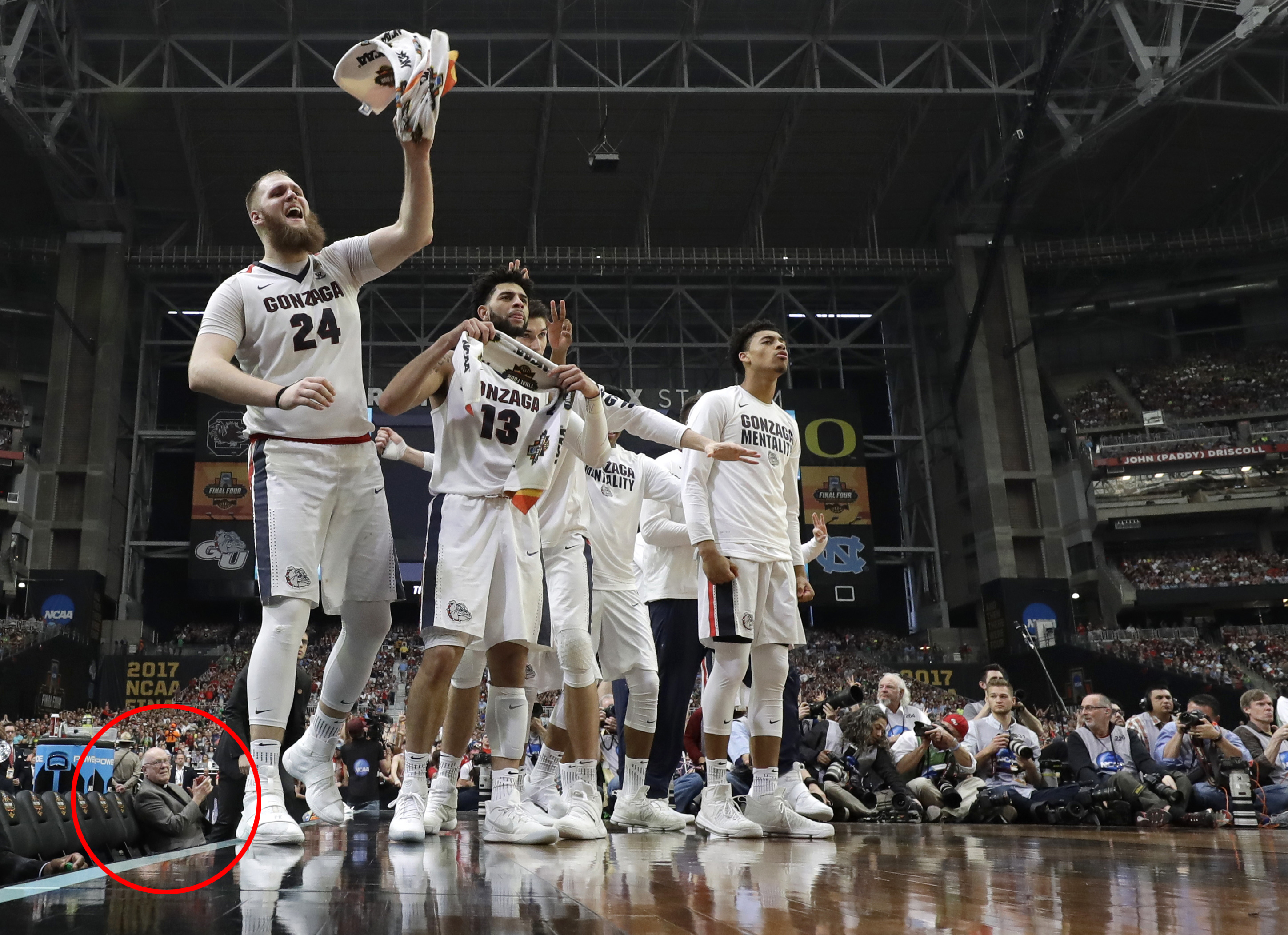 8124acce10e Father Frank Case, seated at left, cheers on the Gonzaga University  Bulldogs at the 2017 Final Four NCAA college basketball tournament.