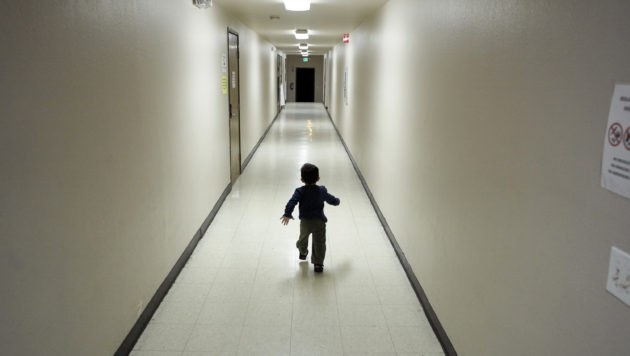 A small boy runs down a long empty hallway on his own.