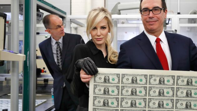 Steve Mnuchin and his wife hold up a sheet of money and smile