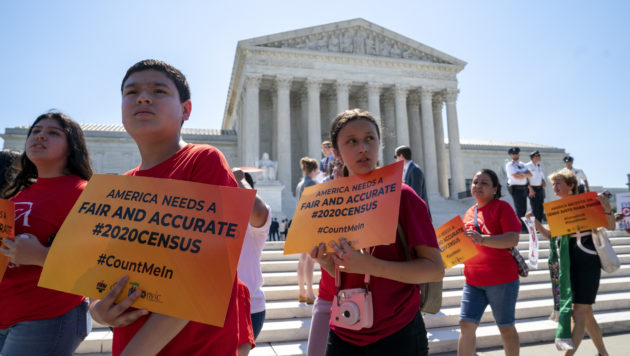 """A group of young demonstrators walk outside the Supreme Court, holding signs that say """"America needs a fair and accurate #2020Census"""""""