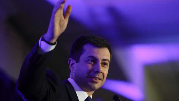 Pete Buttigieg smiles and waves from a stage with a purple background.