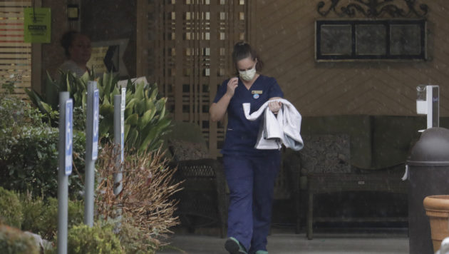 A worker in scrubs at the Life Care Center in Kirkland, Wash., wears a mask as she leaves the building.