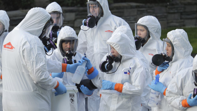 Workers from a Servpro disaster recovery team wearing protective suits and respirators are given supplies as they line up before entering the Life Care Center in Kirkland, Wash., to begin cleaning and disinfecting the facility, Wednesday, March 11, 2020. The nursing home is at the center of the coronavirus outbreak in Washington state. For most people, the virus causes only mild or moderate symptoms. For some it can cause more severe illness, especially in older adults and people with existing health problems.