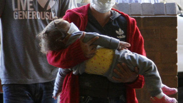 An adult woman wearing a medical mask carries a sleeping child, also wearing a mask, through a crowd of people at immigration court.