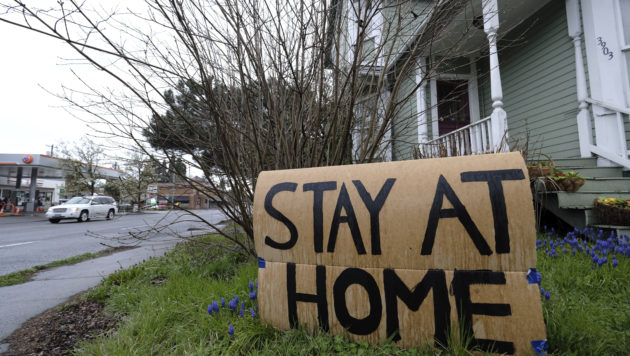 "A cardboard sign says ""stay at home"" outside a house"