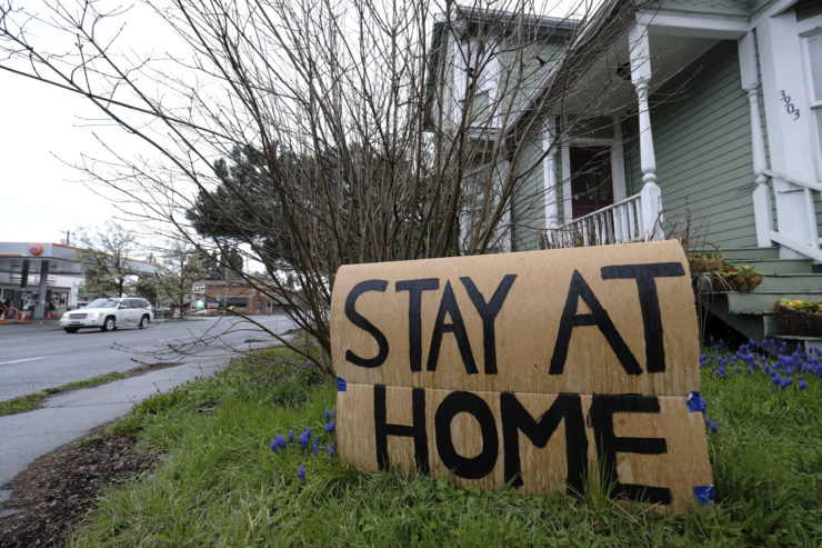 """A cardboard sign says """"stay at home"""" outside a house"""