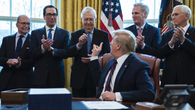Donald Trump sits at his desk in the oval office, with a bill in front of him. He is flanked by an array of advisors, who are all older white men wearing blue suits.